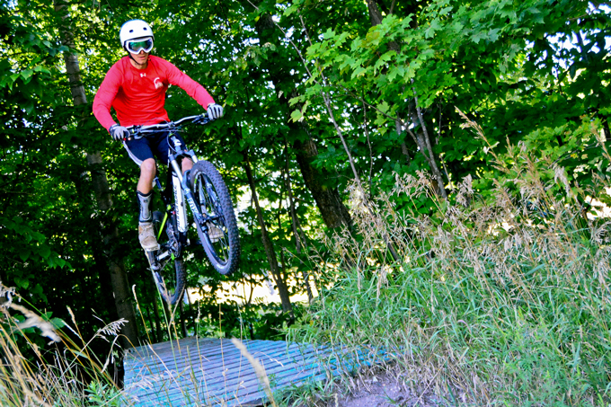 A rider jumps a wood feature at Boyne Highlands Mountain Bike Park.