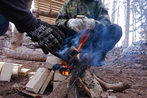 A cozy campfire keeps the trail builders stoked on the mountain.