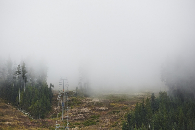 A Whistler chairlift ascends into the fog.