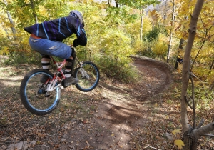 A rider lanches into a berm amidst fall foliage.